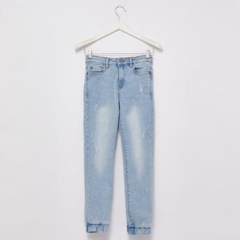 بنطلون جينز ممزق بتفاصيل جيوب وأطراف مطّاطيّة
