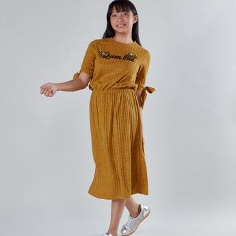 فستان بارز الملمس بتفاصيل ترتر وأربطة