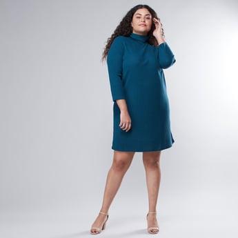 فستان واسع متوسّط الطول بارز الملمس بياقة ضيّقة وأكمام طويلة