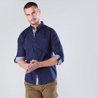 قميص بأكمام طويلة وجيب على الصدر وألسنة تثبيت بأزرار