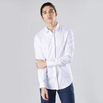 قميص بقصّة سليم سادة بياقة عاديّة واسعة وأكمام طويلة