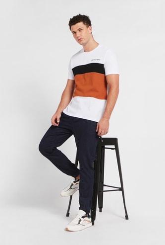 بنطلون جينز بارز الملمس بخصر متوسّط الارتفاع وجيوب ورباط إغلاق