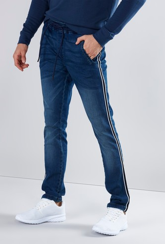 بنطال جينز سادة بقصّة سكيني وخصر متوسط الارتفاع بتفاصيل اشرطة ورباط