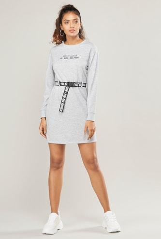 فستان قصير واسع بأكمام طويلة وحزام وطبعات نصية