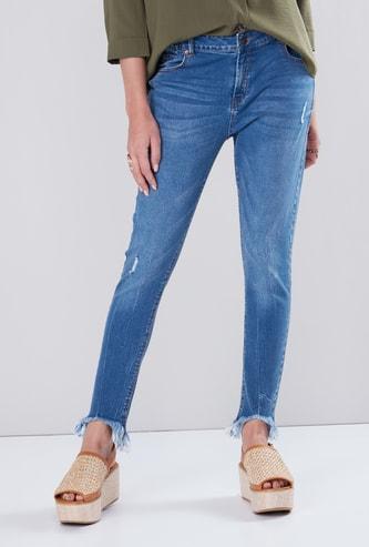 بنطال جينز ممّزق بقصّة عاديّة وجيوب وخصر متوسط الارتفاع