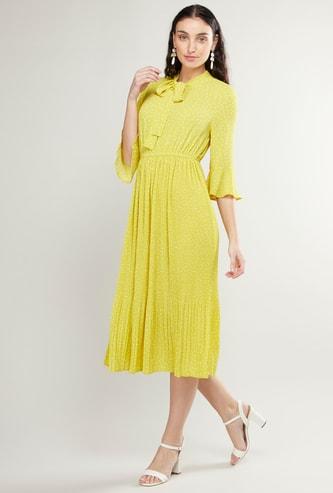 فستان ميدي بطبعات منقّطة وفيونكة وتفاصيل ثنيات