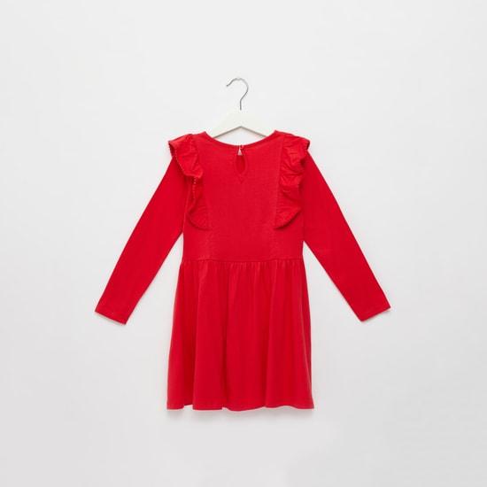 فستان بأكمام طويلة وتفاصيل كشكش وطبعات شعار