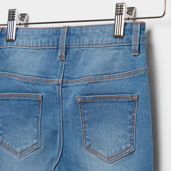 بنطلون جينز بزر إغلاق وجيوب وطبعات شعار