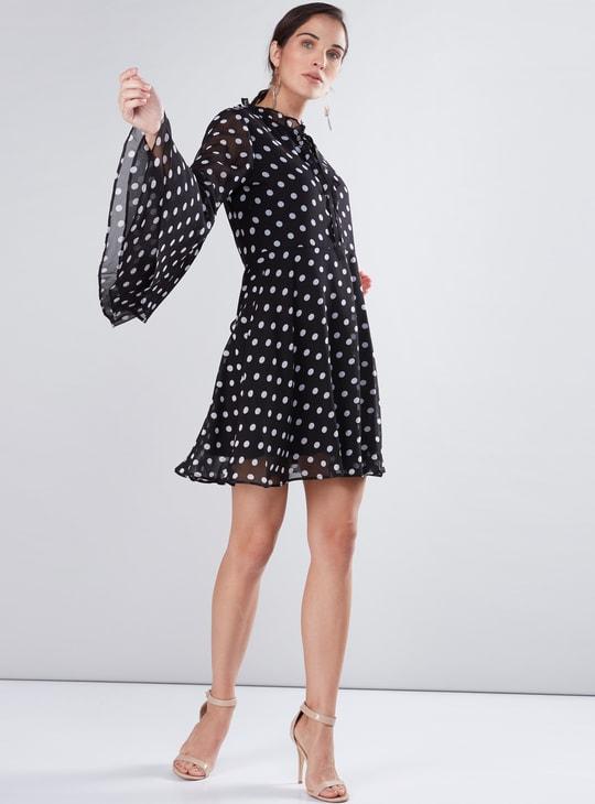 فستان بطبعات منقّطة وفيونكة وأكمام واسعة