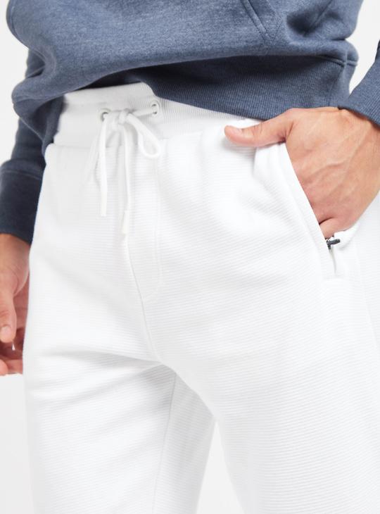 بنطلون رياضي بقصة سلّيم متوسط الارتفاع مع جيوب ورباط إغلاق