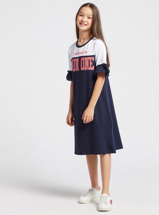 فستان بأكمام قصيرة وطبعات نصية وتفاصيل كشكشة