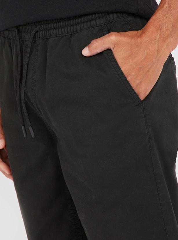 شورت سادة بخصر مطّاطي متوسّط الإرتفاع وتفاصيل جيوب