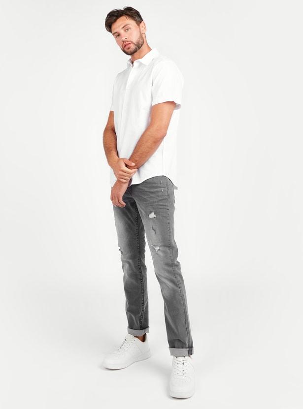 بنطلون جينز ممزّق بقصة سليم و خصر متوسط مع جيوب وحلقات للحزام