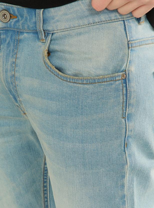 بنطلون جينز ضيّق بـ5 جيوب وزر للإغلاق وبنمط باهت