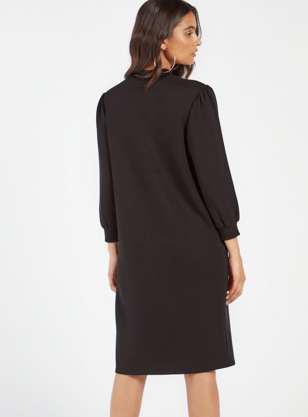 فستان واسع بتفاصيل نصيّة مطرّزة وياقة عالية وأكمام بيشوب