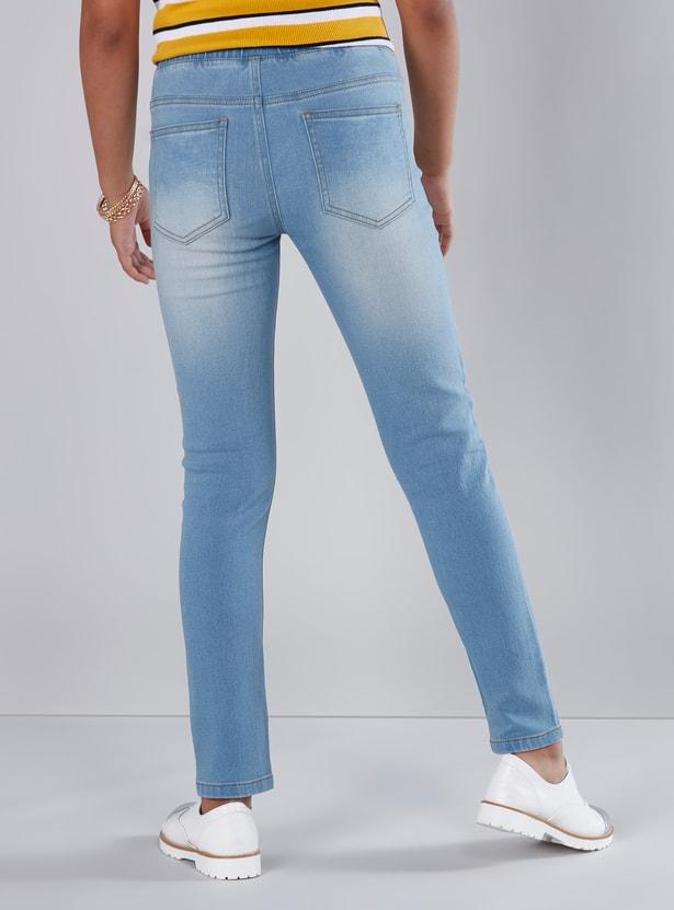 بنطال جينز طويل بقصّة ضيّقة وخصر مطّاطي وجيوب